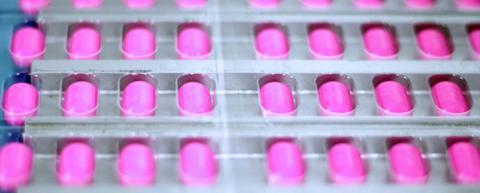 Pink pills being manufactured in a pharmaceutical plant