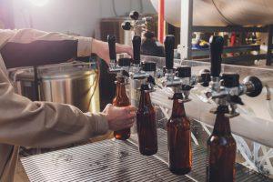 spilling beer into glass bottles